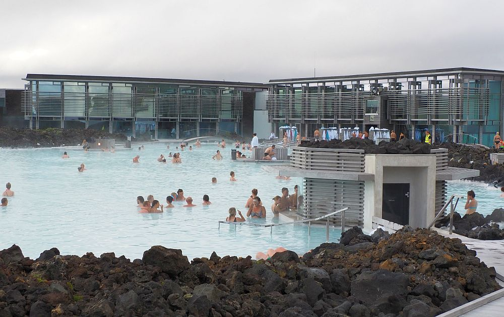 The water of the blue lagoon is milky blue, edged with black volcanic rock. Beyond the water is the modern spa building with lots of glass.