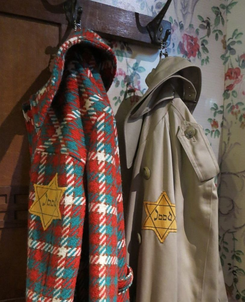 """Two coats hang on a coatrack. The left-hand one is brightly checked in red, green and white. The right-hand one is a trenchcoat in beige. Both have a yellow star of David on the sleeve with the word """"Jood"""" inside it, which means """"Jew."""""""
