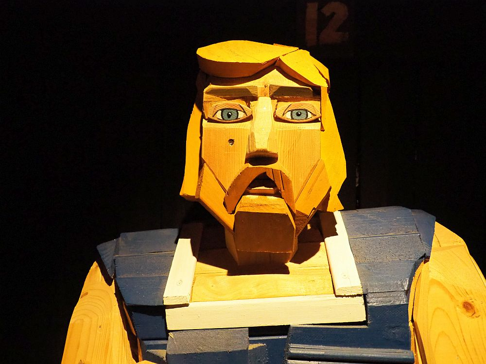 A human figure made of wood. Here only photographed from the chest up. It is a man with blond hair and a mustache and beard. The figure is expressed in rough-edged shapes of wood in different colors, almost impressionistic.