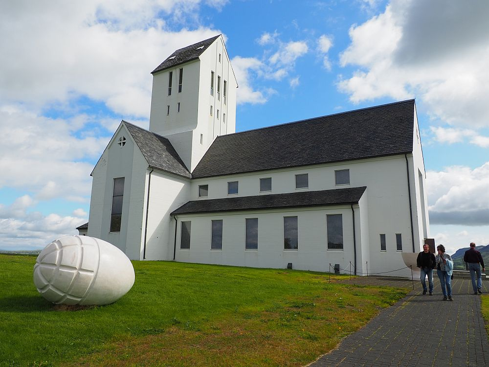 The church is white with a square tower and a grey roof, here seen from the side. On the grass next to it is a large egg, also white, with some ridges carved into one end. The egg is huge, probably about a meter across. 3-week Iceland itinerary