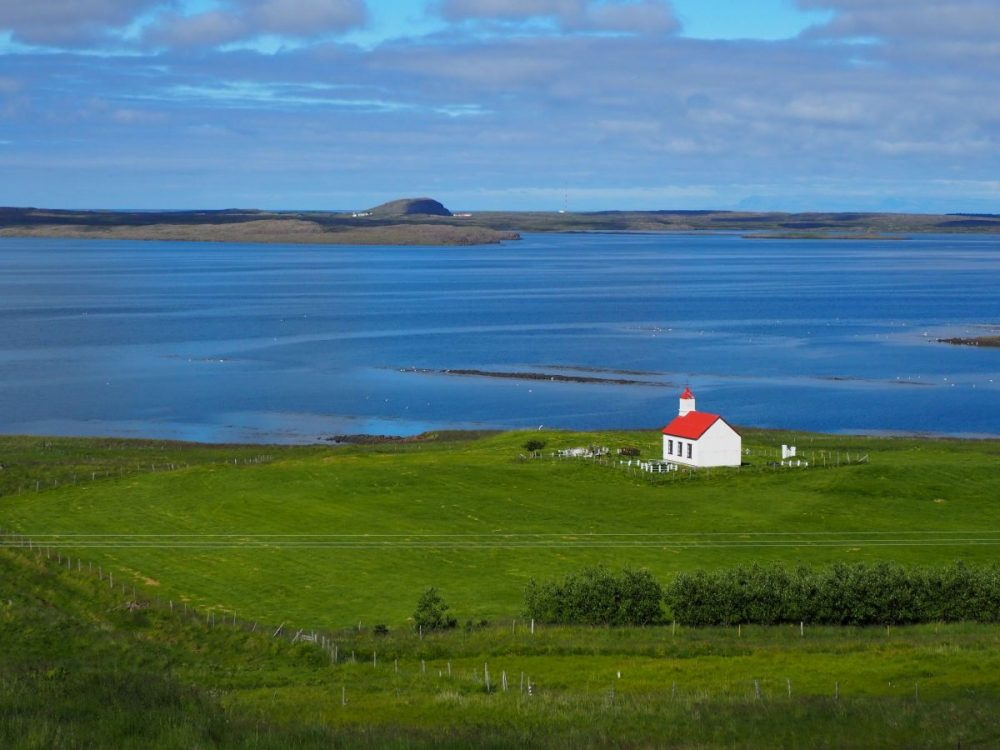 A green field in the foreground, blue sea beyond, with some low land on the other side of a bay. In the field is a white church with a red roof facing the sea. Passed somewhere along the way on our 3-week Iceland itinerary.
