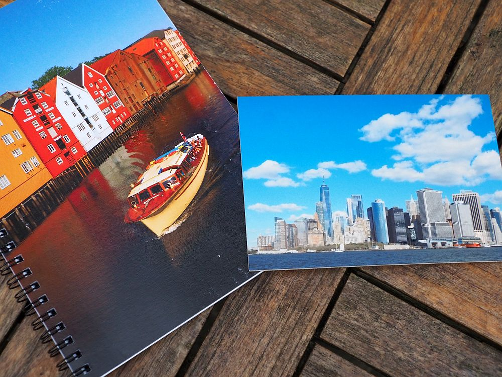 On the left, a spiral notebook with an image of brightly colored warehouses on a canal in Norway, a small boat passing in front of them. On the right, a photo of the New York City skyline against a blue sky with fluffy clouds.