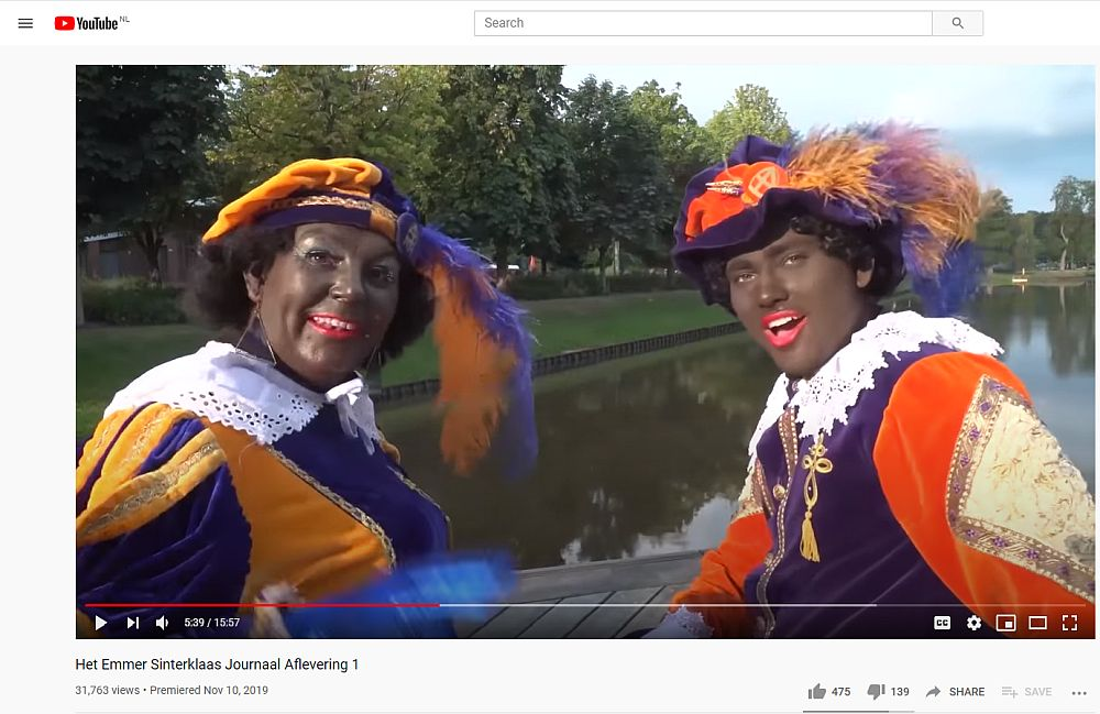 Two Zwarte Piets (Black Petes) smile at the camera. Both wear the typical bright Moorish costume and a beret with a feather. Both are in dark brown facepaint and have bright red lipstick on.
