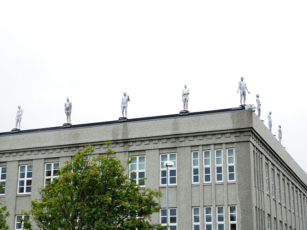 A blockish grey building, probably offices or a school, but right along the edge of the roof are a series of statues of men. All are full-body, white and stand facing out to the street. Each is posed slightly differently. Spotted during our free walking tour of Reykjavik.