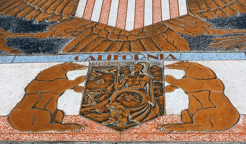 """Inlaid seal shows two bears on either side of the shield. The shield has a classical figure of a Roman(?) warrior and the word """"Eureka"""". Above the seal is the word California."""