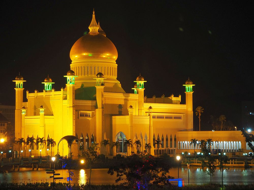 The mosque is pictured at night, light up from below. It has small turrets along its sides and a huge dome in the middle that is covered in gold. Around the building is a row of tall palm trees.