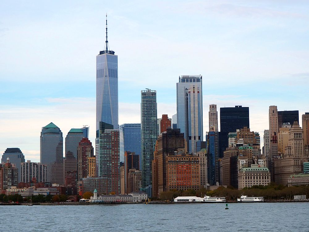 Across the water, a city skyline: the southern part of Manhattan. The tallest building is silver with glass and has a tall mast on the top: the One World Trade Center Building.