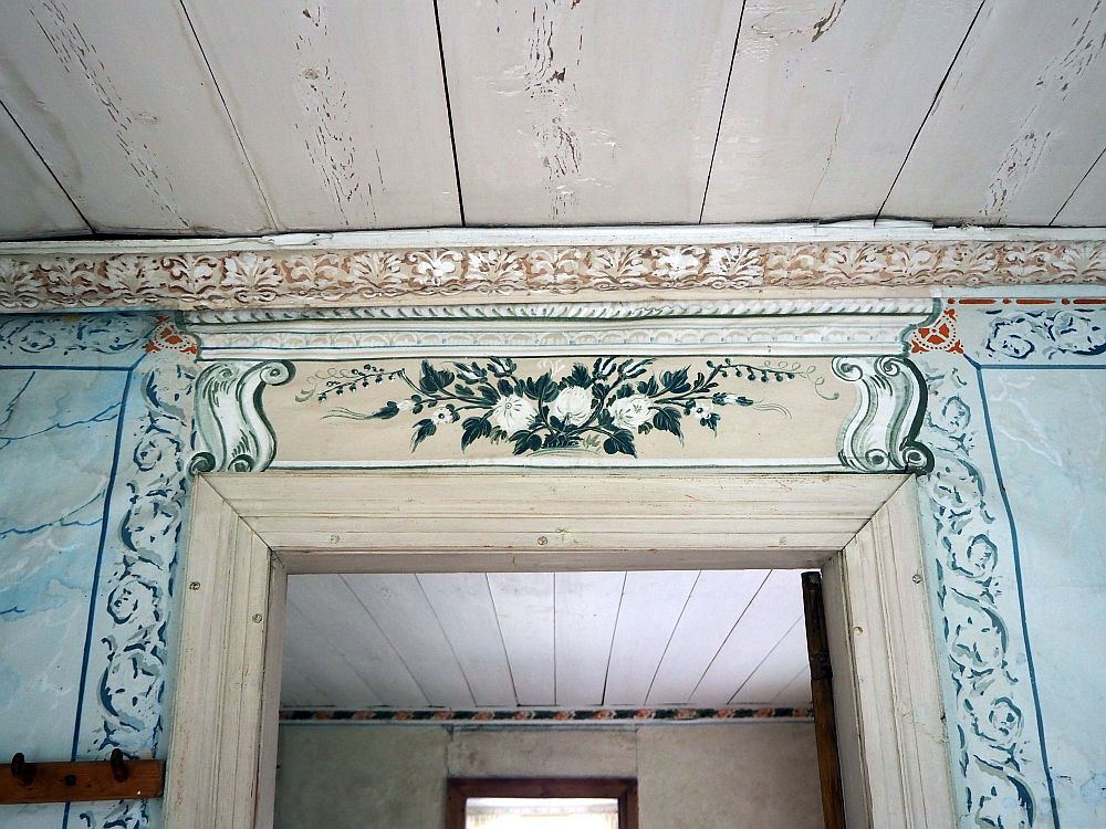 Above the door is a painted set of 3 flowers in white on dark green leaves. Beside the door are some scrolly shapes that I think are intended to be trompe l'oeil carvings.