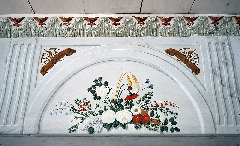 A half-circular arch over the door. White background with an arrangement of wildflowers in white, red and green painted on it. Top left and right are bundles of hay above the arch, each with a collection of agricultural implements. Above the arch is the molding along the edge of the ceiling, which is painted with a repeting pattern of garlands in brown and olive green.