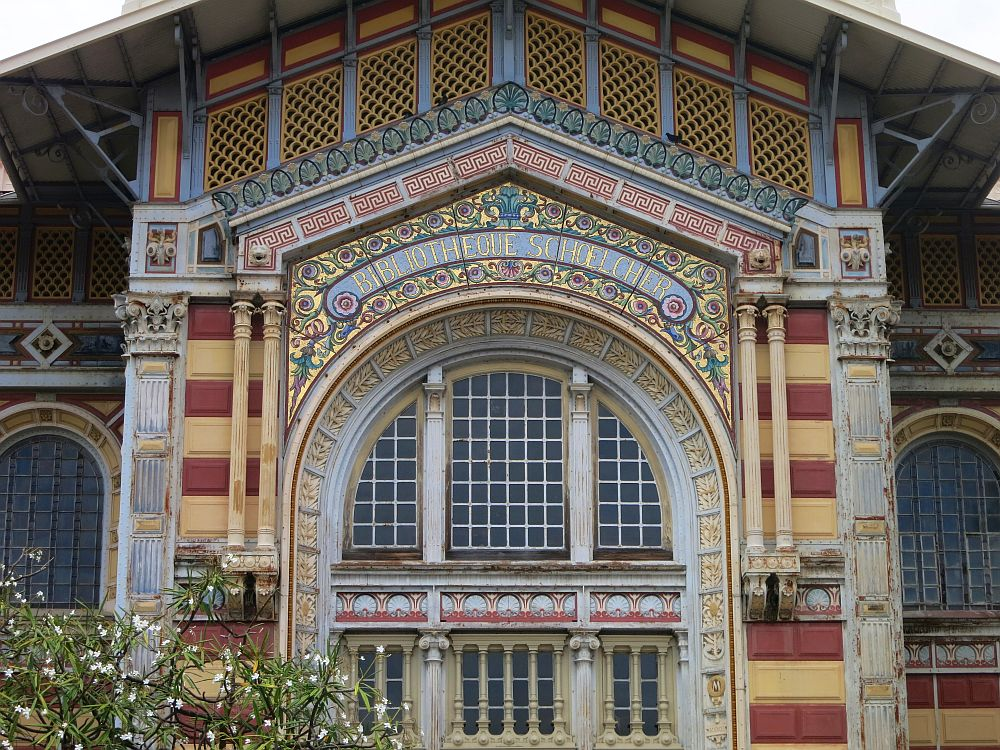A close-up on the exterior of the library shows very detailed and colorfful art nouveau tiling covering every inch of the exterior. Shown is one arched window and the decoration above and beside it.