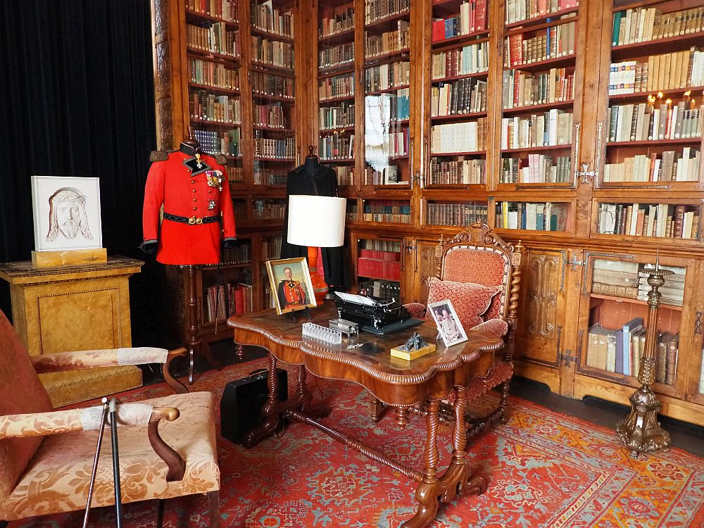 A large wooden desk with an upholstered seat behind it and another in front of it. A typewriter and some framed pictures on the desk and a bright red uniform on a stand next to it. Behind the desk the wall is filled with glass-fronted wooden shelves filled with books.