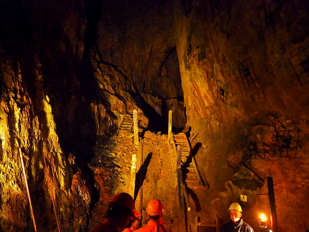 The heads of several people are visible at the bottom of the photo, wearing hardhats of orange or yellow (the tour guide). Indirect lights reveal two parallel stairways up a slope to a tunnel that disappears into darkness. The stairways are wooden with a broken railing on the side between the two stairways. ON the outside is rock walls. The stairway on the left is partly covered in rubble The one on the right has a broken tread toward the top and rubble toward the bottom.