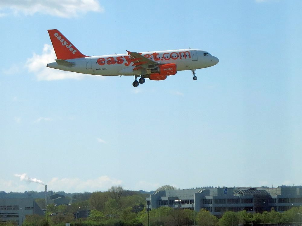 Against a blue sky, flat land at the bottom of the picture, wooded. Center top: an EasyJet plane comes into land, its landing gear almost fully lowered.