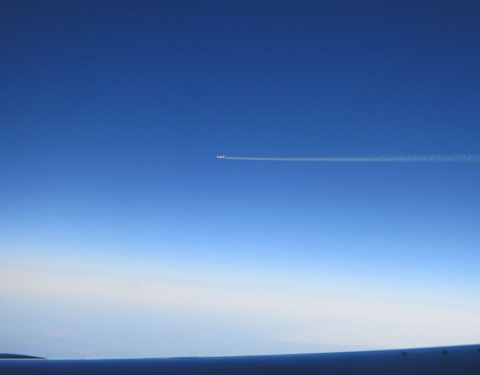 A deep blue sky, with the top of an airplain wing along the bottom of the photo. A tiny airplane in the center, with its smoke a horizontal line from the middle to the right edge of the photo