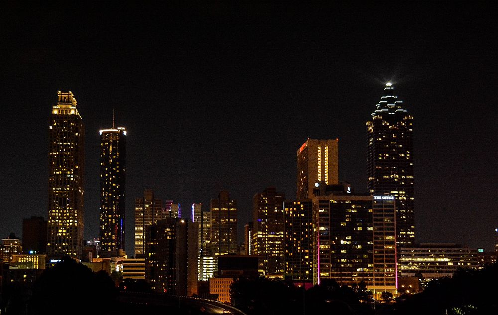 A nighttime view of the city: a jumble of tall buildings with lights in their windows. A weekend in Atlanta.
