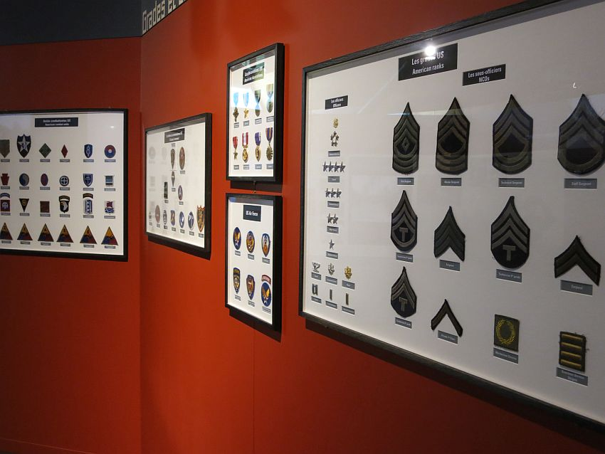 A deep red wall with a series of frames hanging on it. Each frame is filled with various insignia and medals: all things that would be attached to a uniform. The nearest one is filled with the insignia of the different American ranks in the military: shoulder patches and pins, each mounted and labeled.
