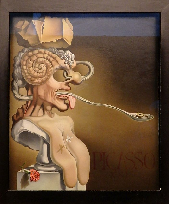 """A human bust, on a pedestal, seen from the side. It has gaping holes for eyes, a nose that extends around and back through the hole, a curled thing like a ram's horn on the side of its head. The white hair forms a sort of ponytail on the back of the head that extends into the neck and out the mouth on the other side. It entends much farther than the tongue (which also sticks out). At the end of the """"hair"""" is a spoon, that seems to hold a tiny lute. The figure has rock on its head."""