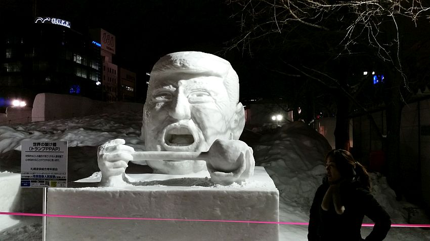 It's nighttime at the Sapporo Snow Festival, but the snow sculpture at the center of the picture is well-lit. It is a huge head that resembles Donald Trump with his mouth wide open. His hands show in front of his chin holding either end of a gavel or hammer, also all made of snow.