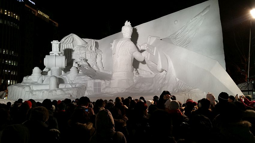 This snow sculpture at the Sapporo Snow Festival refers to some story I am not familiar with. It is absolutely huge, judging by the people who are visible at the bottom of the photo. The sculpture shows a large man onthe right with is back to the photo, perhaps with a chicken's head? He is showing from the hips up and wields a sword larger than he is by far. It appears to extend out of the sculpture into the audience. On the left is another figure further back, a human in a hooded cloak.