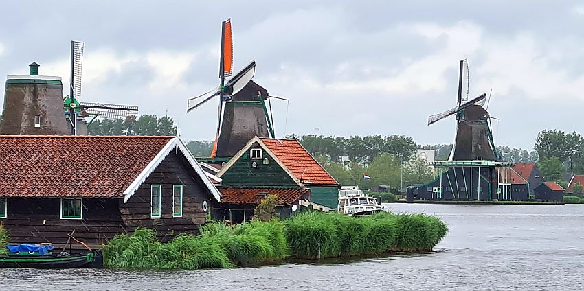 Seen across the water, three windmills, the nearest one with sails, and two low houses in front of it on the riverbank.