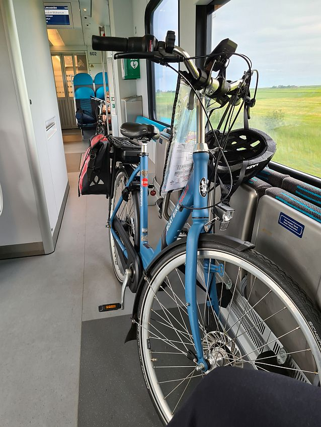 The bicycle leans against a window, where a flat green field is visible. A helmet hangs from the handlebar.