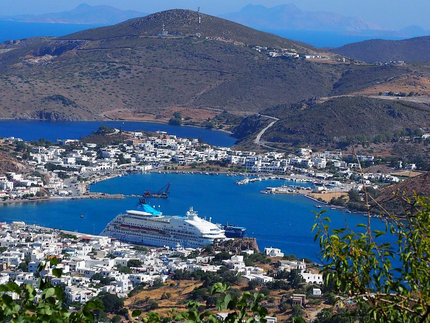 Looking down from a hill to Patmos harbor: blue water surrounded by land covered with white buildings. The ship towers over the nearest buildings. Beyond the harbor is a mountain with very few buildings on it.