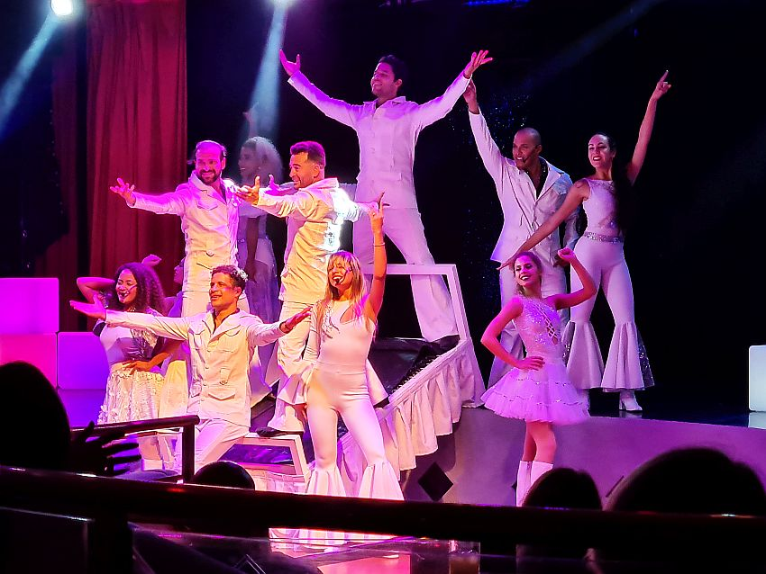 9 people - 5 men and 4 women, hold their hands up and pose, facing the audience. They are all wearing white clothing in a 70s style, e.g. exaggerated bell-bottoms.