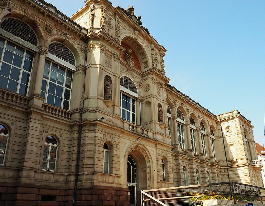 The facade of the building is neo-classical, with arched windows and pillars between them. Above the entrance in the center are numerous statues in niches or worked into the facade. Decorative images line the roof line too. The building is a tall two stories and houses one of the older European hot springs.
