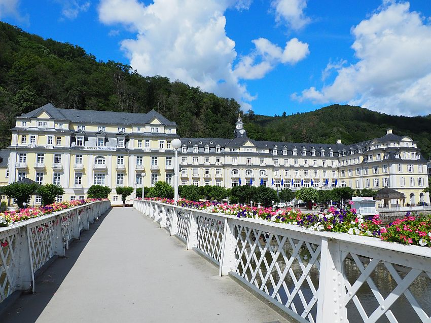 The hotel is large and not symmetrical, with the left-hand end larger than the right. This photo sights down a bridge edged with colorful flower boxes on white railings. The hotel is five stories high with large vertial windows especially on the 2nd, 3rd, and 4th stories, where most windows have a small balcony. It is painted light yellow with white trim and a grey roof.