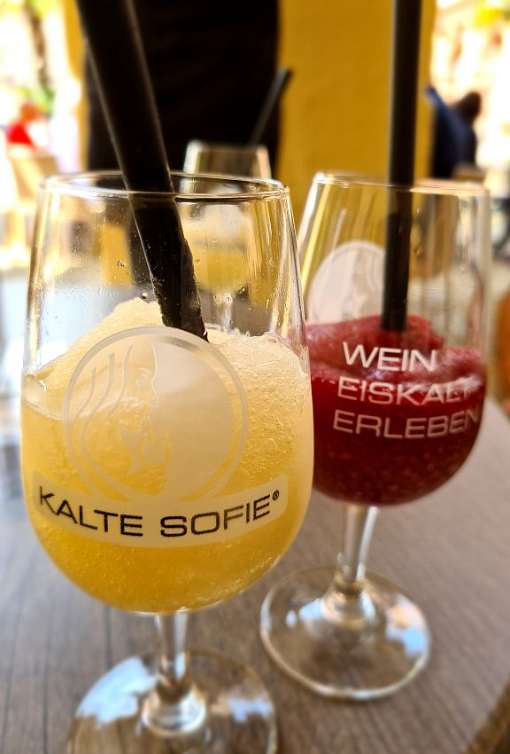 """Two glasses of Kalte Sofie in wine glasses with straws. In front, the white wine version looks like a lemon slushy. Behind, the red wine version looks like a cherry slushy and says """"Wein Eiskalt Erleben"""" which I think means """"Experience ice cold wine""""."""