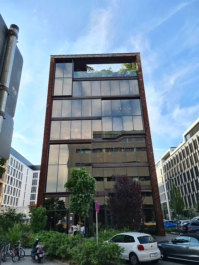 A rectangular building, not very wide, but about seven stories high. The front is glass and reflects the building opposite, that also looks like an office building. Around the stories and the sides of the building are in dark red brick or stone. The top floor has a balcony of sorts that does not have a roof, so it is a partial roof garden, even if it's not on the roof. On the street, a few trees and bushes, parked cars and bicycles.