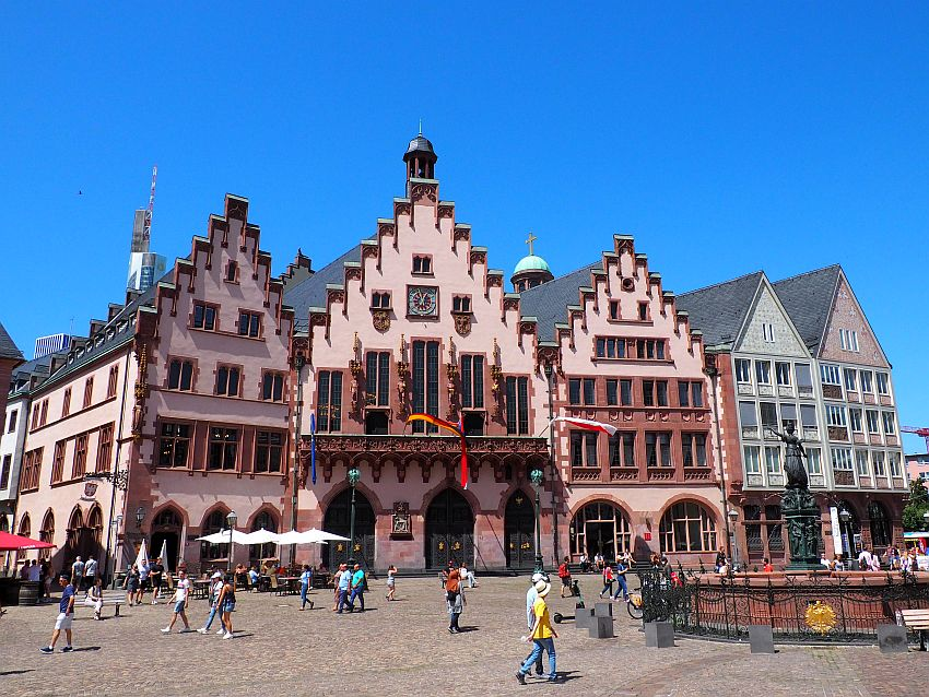 Each of the three buildings has a stepped gable up to a point. They're all painted pale pink while the trim is a darker pinkish-red. The ground floor entries and windows all have arches over them. The middle building has small sculptures between and around the windows on the upper stories. In front of them on the square, people pass by and there is a fountain with a statue of justice holding a scale.