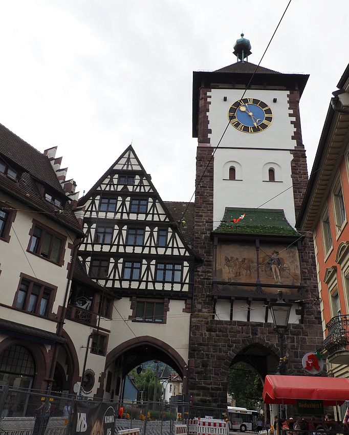 The tower is square and white, with brick on the corners. There's a big clock just under the rather plain roof. Lower down is a large painting of a person and some horses - the painting spans the width of the tower. Next to the tower is a half-timbered building with a pointed roof. Both buildings have large archways on the ground floor, big enough to let cars through.