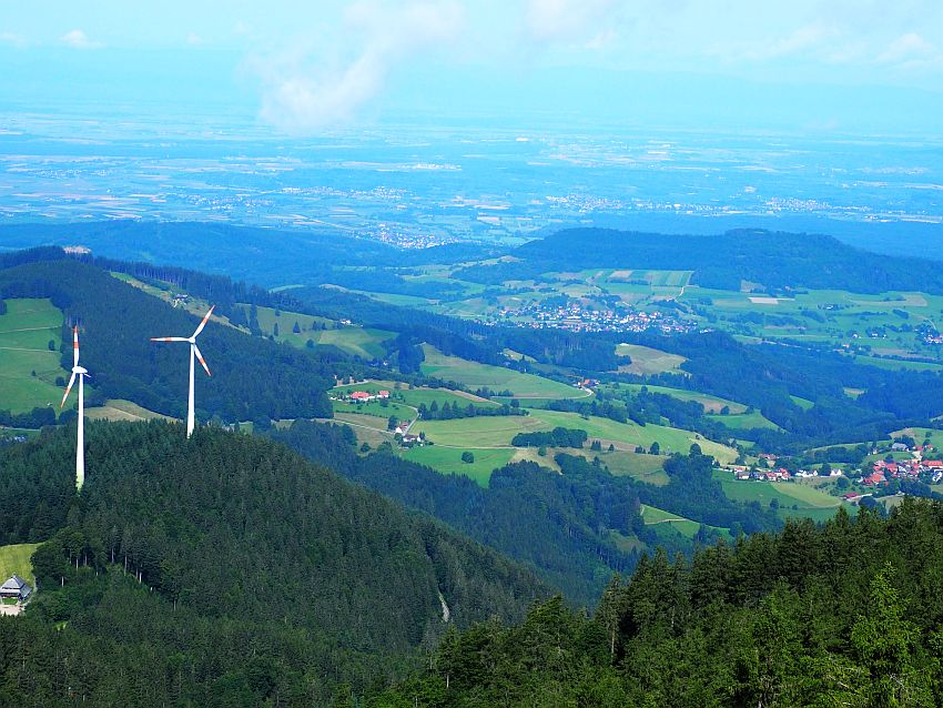 Foreground: the tops of tree-covered hillls, the left one has 2 large windmills on top. Beyond that, hilly terrain with a mix of green farmland, small villages and wooded areas. In the background, more of the same mix, but less distinct because of the distance.