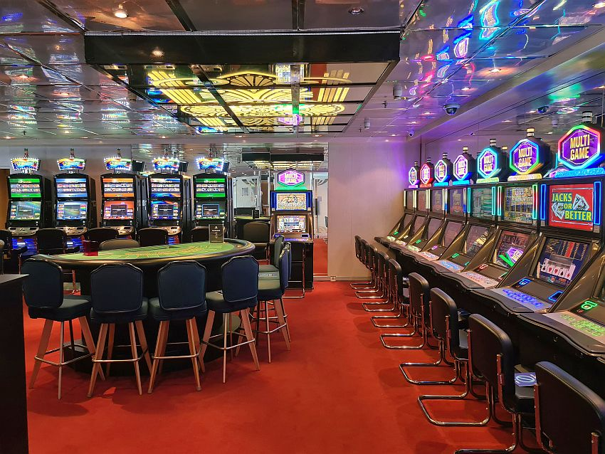 On the right wall and the back wall, rows of slot machines, each with a chair in front of it. In the middle of the room, semi-circular table with chairs around its curve. It looks like it's intended for blackjack. The slot machines all are lit up with bright lights, which reflect from the shiny ceiling.