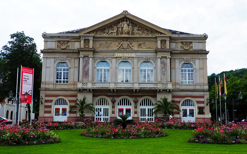 The theater in Baden-Baden, one of the better-known European hot springs towns. It is neo-classical, with pillars between the windows, which have arched tops. The whole building is about 3 stories tall and symmetrical, with 5 windows across on ground and 1st floor. The top floor has an ornate pediment with detailed baroque style statues and bas-reliefs. In front of the building are some neat and colorful flower beds surrounded by grass.