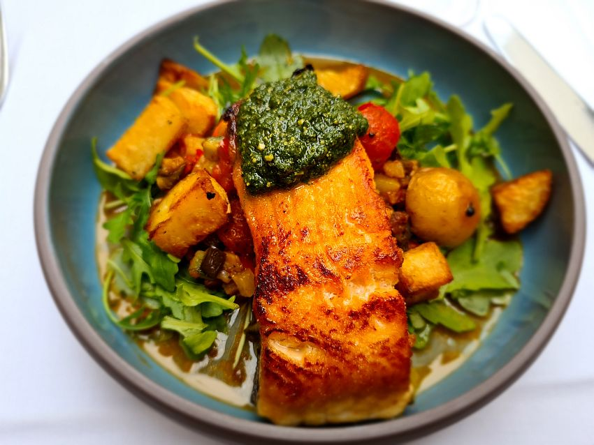 A plate of food. Salmon with a green sauce at one end. The salmon sits on some mixed stewed vegetables and roast potatoes, and it all sits on a bed of rucola or similar.