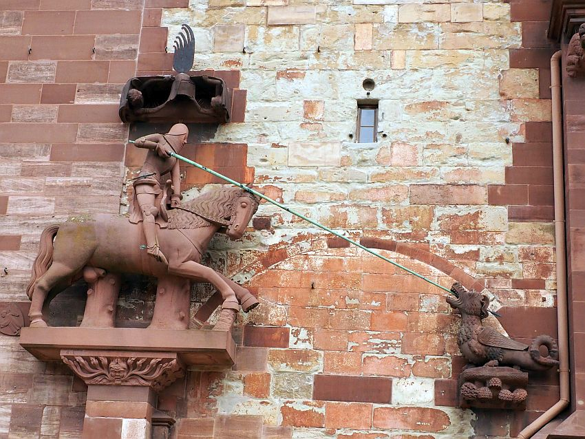 Against a reddish stone wall where the bricks are clearly a range of ages, the St. George statuel. On the left is a knight in armor (St. George) on a horse, carved from red sandstone. He holds a metal lance, longer than the horse's length. It extends to a separate statue of the dragon, facing him, with the lance in its moutn. It is very small compared to the horse, and has a small curled tail.