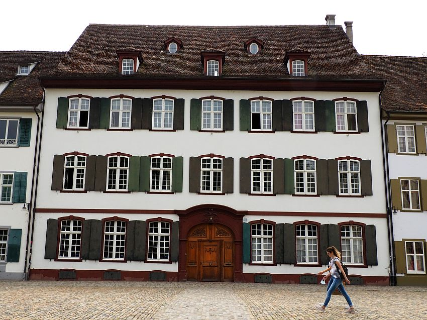 A typical Basel house: simple white plaster, with rows of windows, each with green shutters open around it. The door is large and arched right in the center of the front. Three stories, plus one in the roof. Exactly symmetrical, with 7 windows across each of the upper stories.