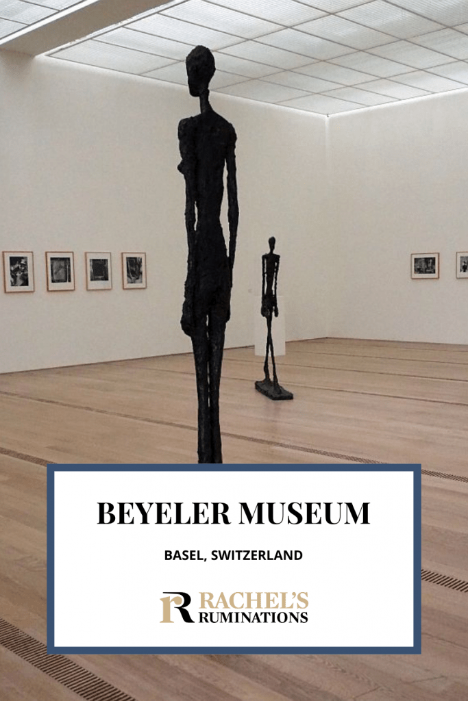 Text: Beyeler Museum, Basel, Switzerland. Image: A Giacometti standing figure with another Giacometti figure in the background.