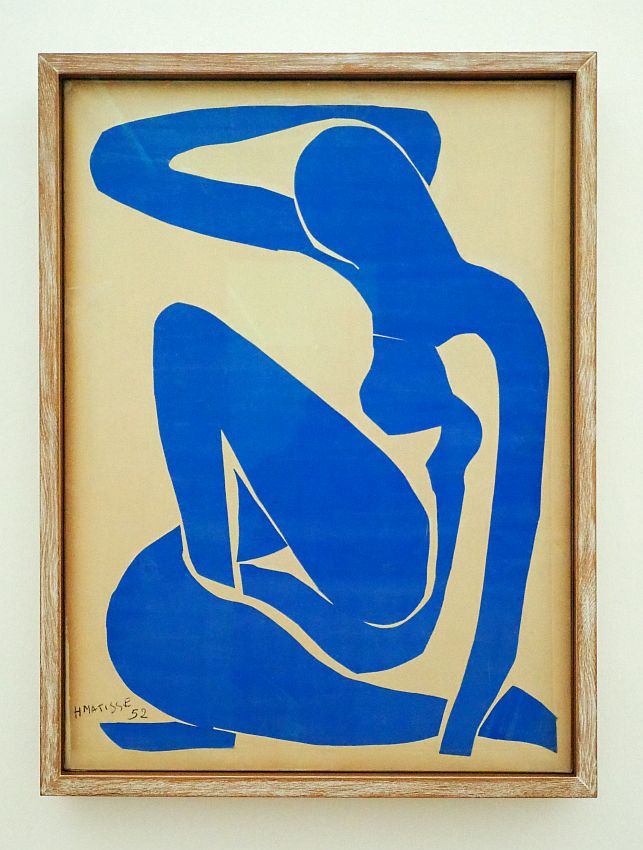 An abstract series of blue cutouts make the general shape of a woman. She sits with one knee up and the other leg curled around her on the floor. One arm touches the floor, while the other is bent up and almost touches the back of her head.