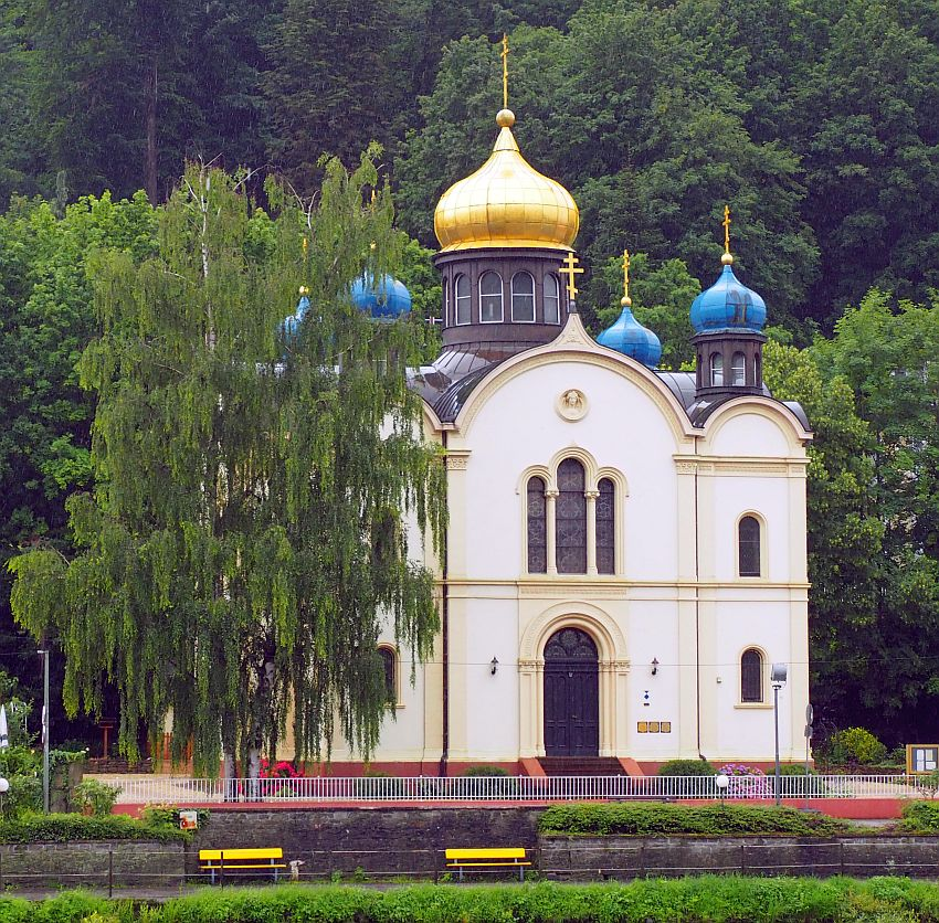 A square building, white on the sides, with arched windows and central doorway. On top, a number of blue-painted onion domes, each with a Russian orthodox cross on top, painted gold. The central tower is topped with a gold-painted onion dome, also with a Russian Orthodox cross on top.