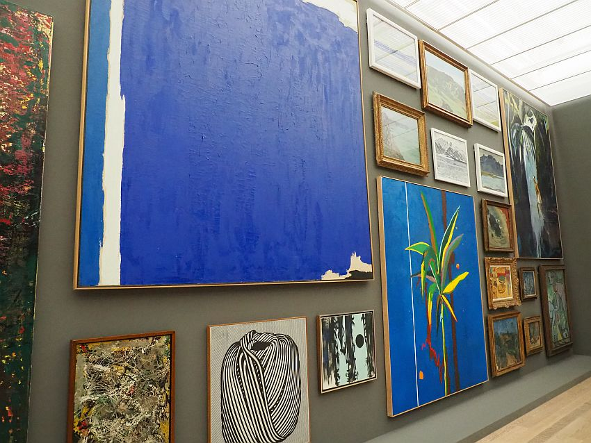 A look down a wall in the Beyeler Museum filled with paintings. It shows, in this one section, 18 paintings.