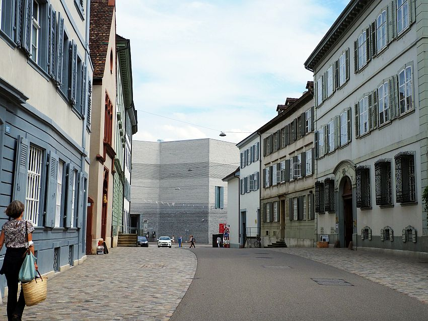 A fairly wide road with cobbled sidewalks on either side. Buildngs on both sides are 3 stories high and very simple, painted in pastels and with shutters around the windows. The road ahead curves slightly left. At the end, a grey wall, not flat but with a few angles in it. It's about the same height as the buildings in the street.
