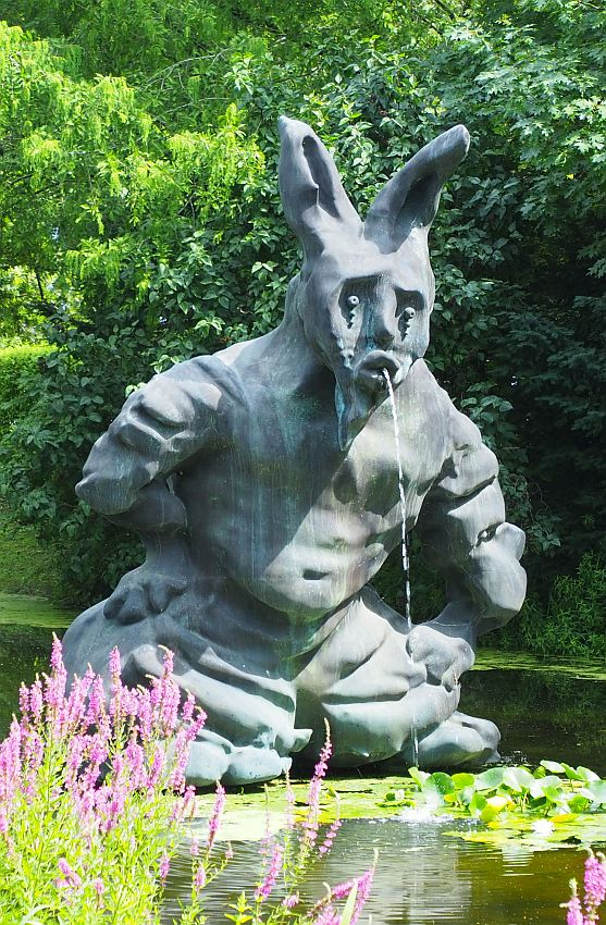 The fountain is in the shape of a person, but very chunky and undefined, sitting or crouching on the water. The head has a human face and rabbit ears and looks sad. The water of the fountain flows from its mouth.