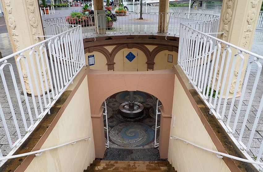 A stairway down one flight, rails on both sides. Below, an arch, through which a mosaic floor is visible with a blue spiral pattern. A round fountain stands in the middle.