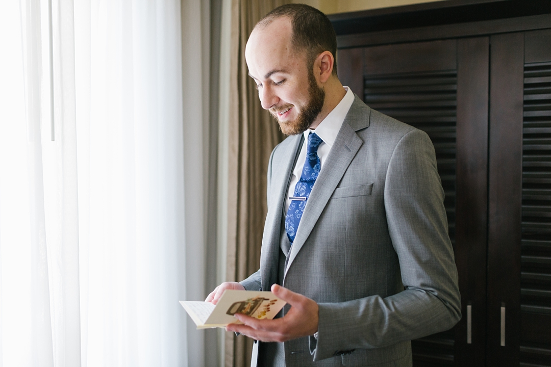 groom stands by window and reads a letter from his bride