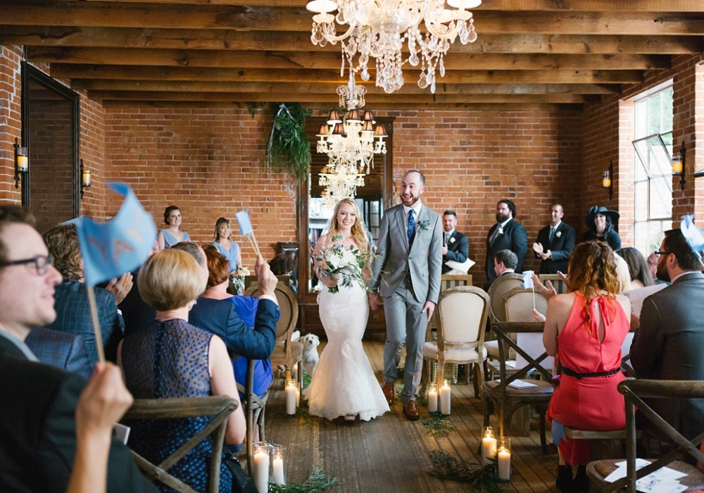 bride and groom walk happily down the aisle at carondelet house