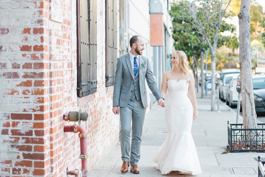 bride and groom walk holding hands in urban setting