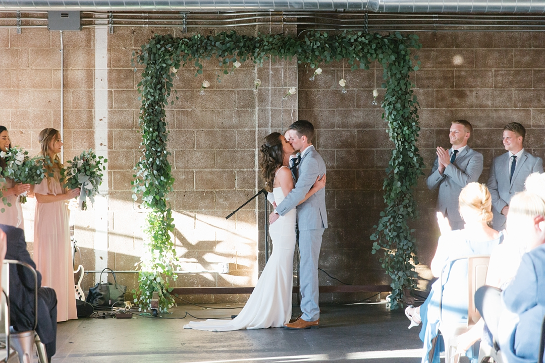 bride and groom share first kiss at smoky hollow studios